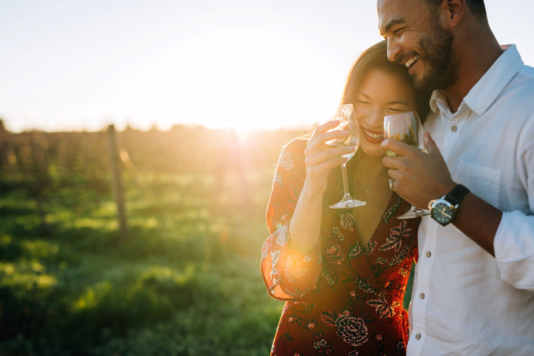 Couple hugging and drinking red wine at a vineyard.