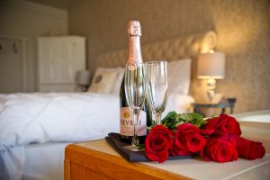 Champagne and flowers on table in Rose Sunset room.