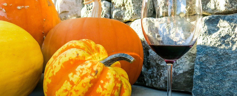 Glass of red wine next to bright orange pumpkins.