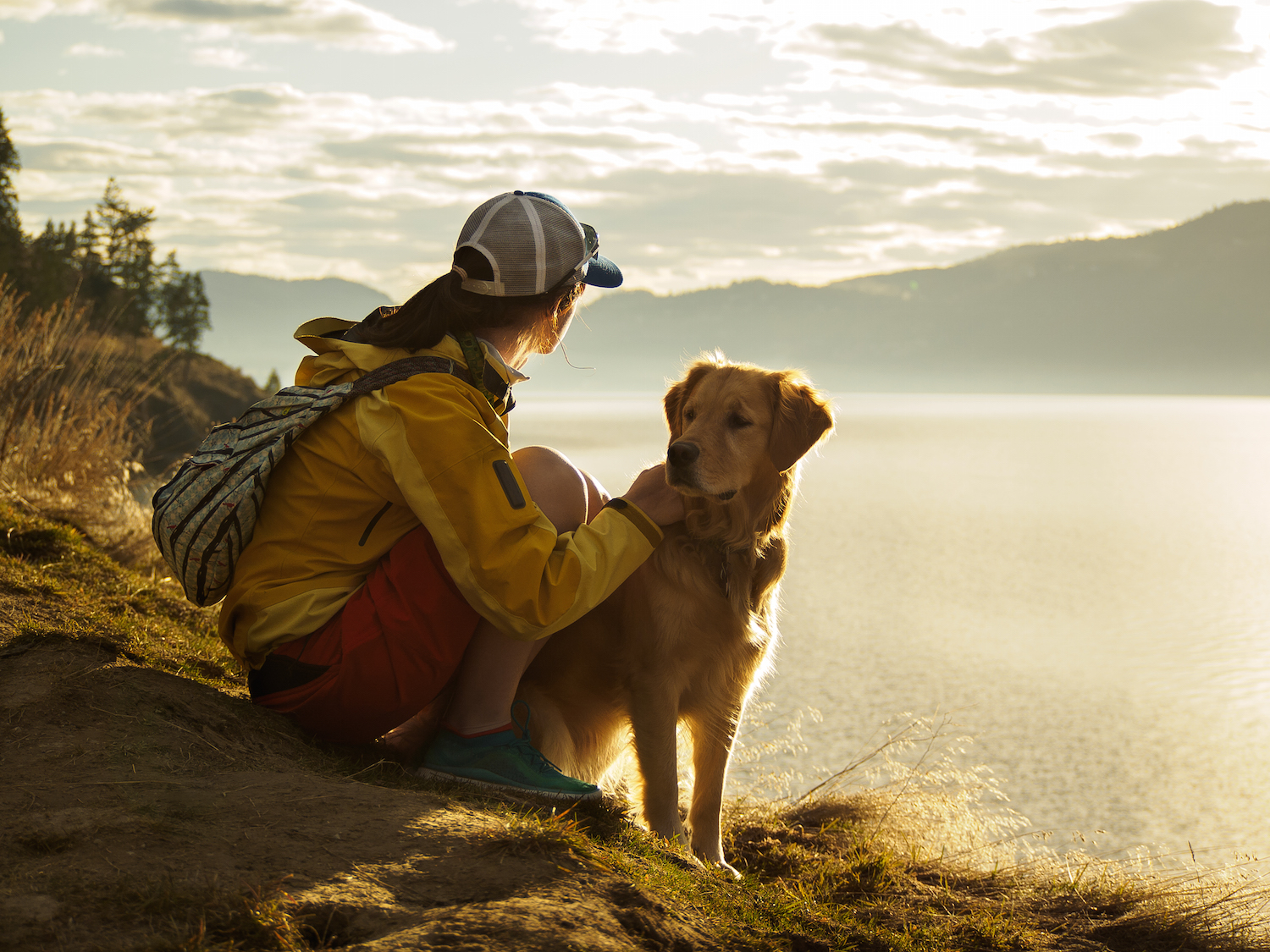Woman hiking with a dog.